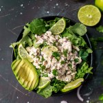 over head photo of cilantro lime chicken, sliced avocado in black bowl on black background, limes on the side