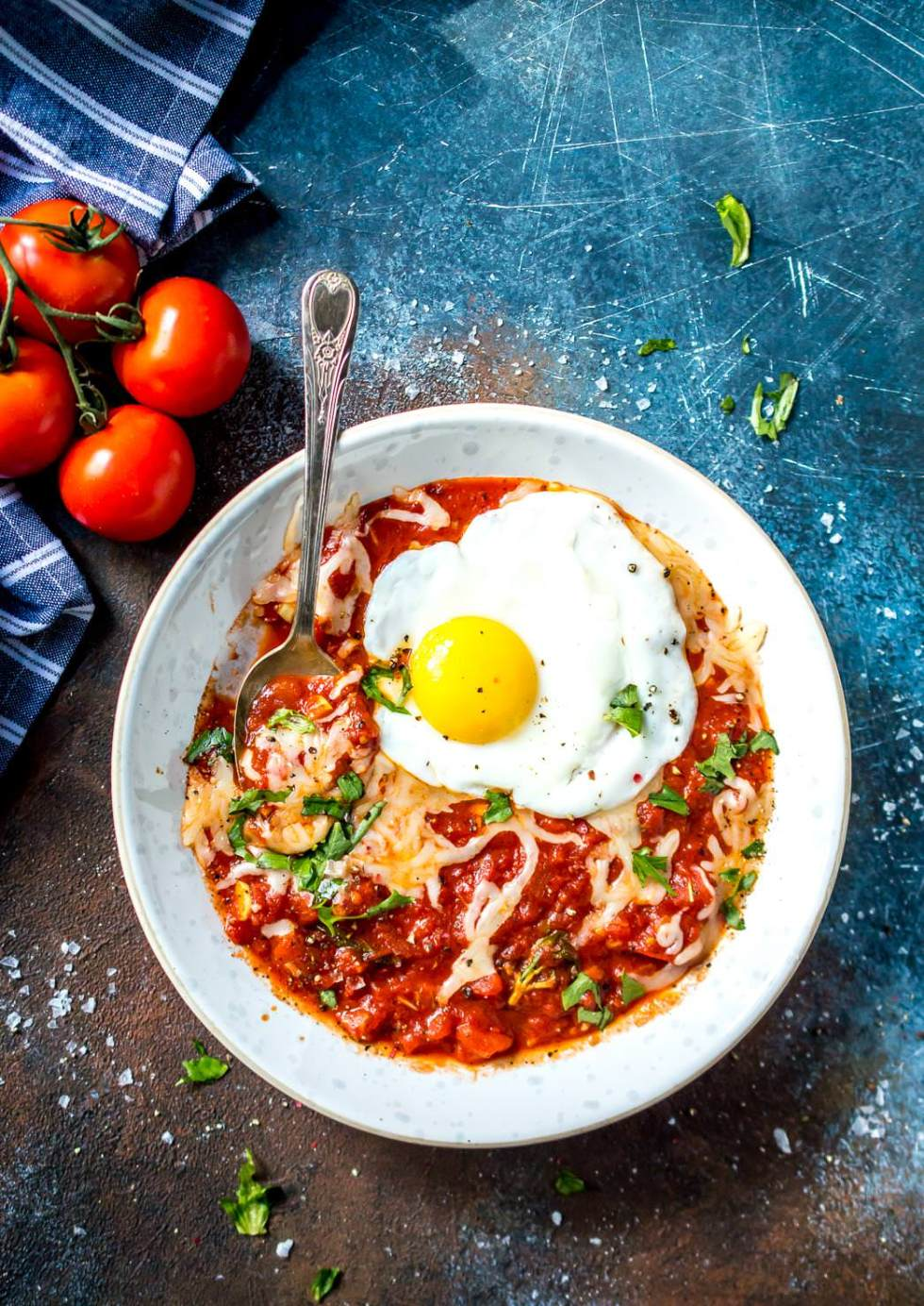 overhead view of white bowl filled with fried egg in purgatory, vine tomatoes on the side