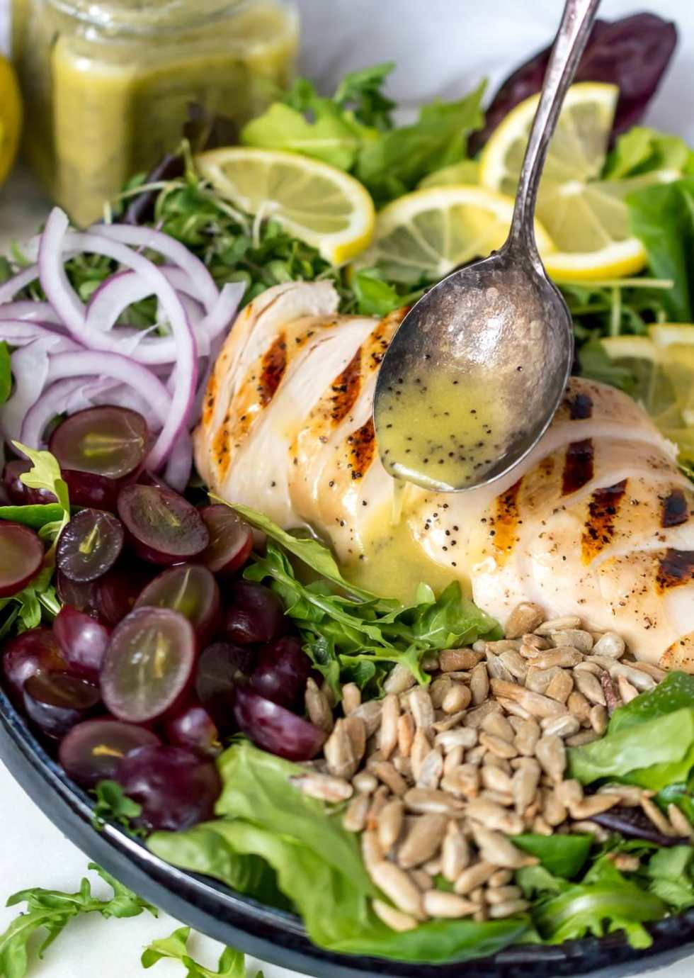spoon drizzling lemon poppy seed dressing over grilled chicken salad