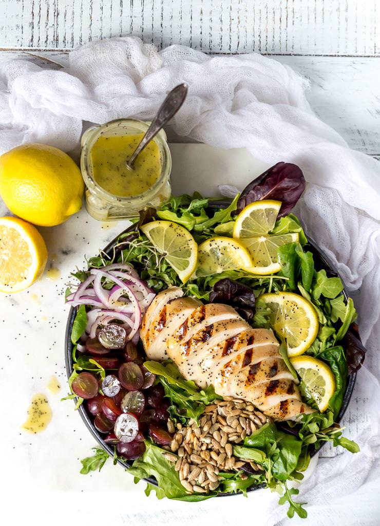 over head photo of grilled chicken salad, lemon poppy seed dressing and lemons with white background