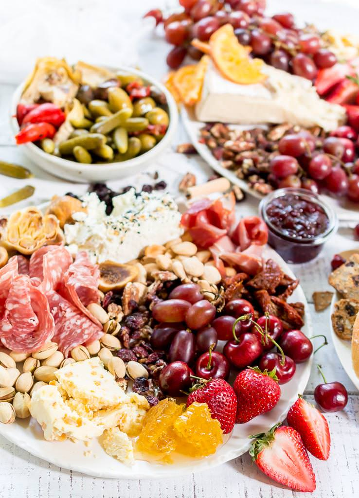 Throw an EPIC Summer Party without even turning your oven on! This Charcuterie Board and Orange 75 Cocktails are perfect for entertaining. The cheese platter is is loaded with meats, cheeses, crackers, fruits, nuts and more. And this simple cocktail recipe is sure to impress your guests! #entertaining #partyideas #cheeseboard #cocktailrecipes