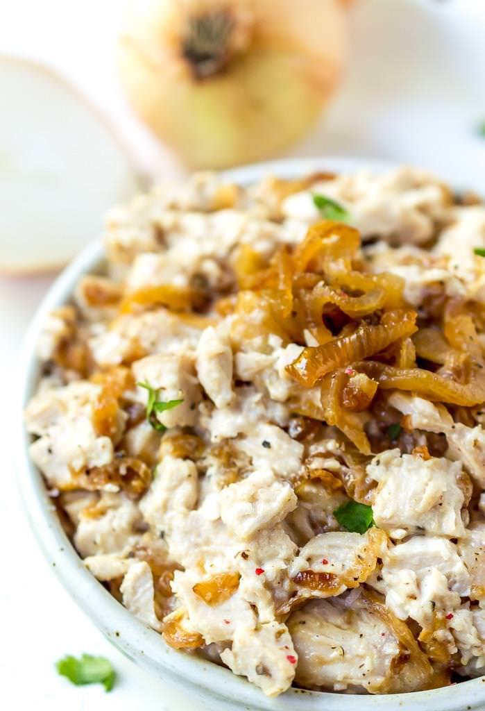 close up photo of caramelized onion paleo chicken salad with white onions in the background