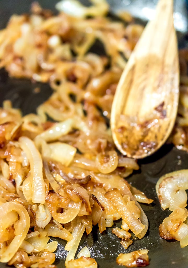 caramelized onions in saute pan being stirred with wooden spoon