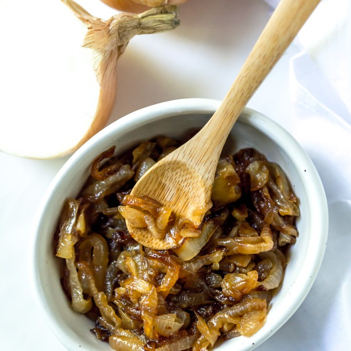 white bowl filled with caramelized onions and a mini bamboo serving spoon