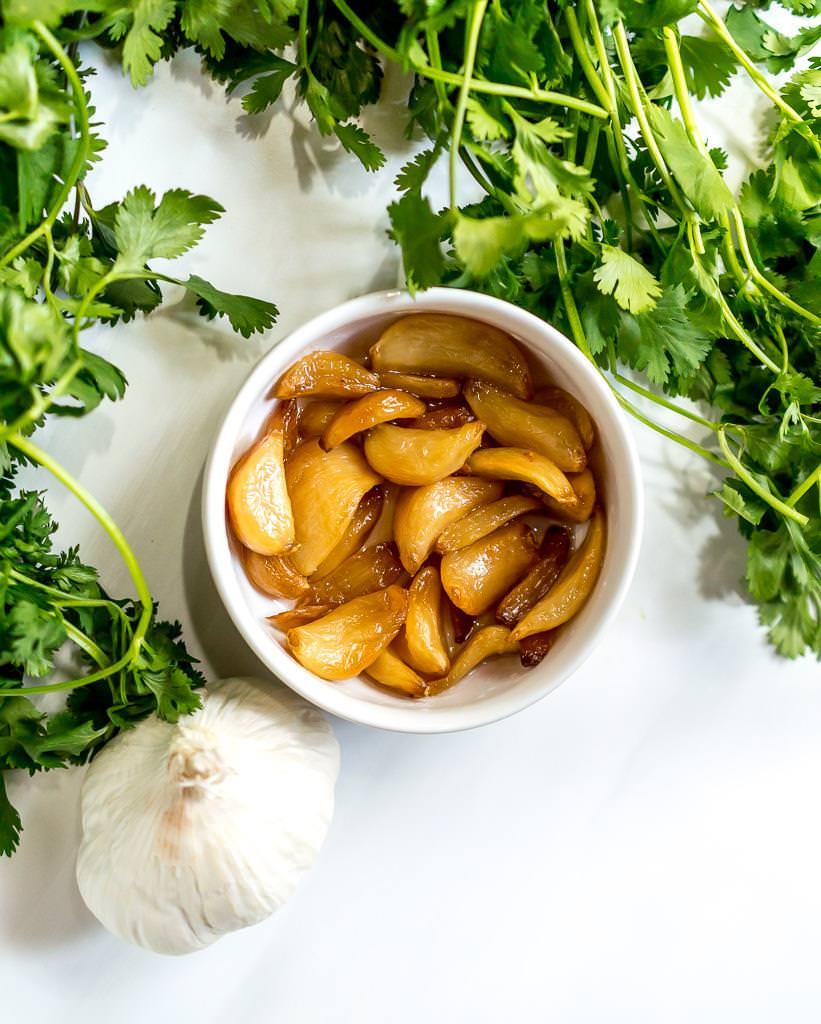 close up photo of roasted garlic and cilantro for chimichurri sauce recipe