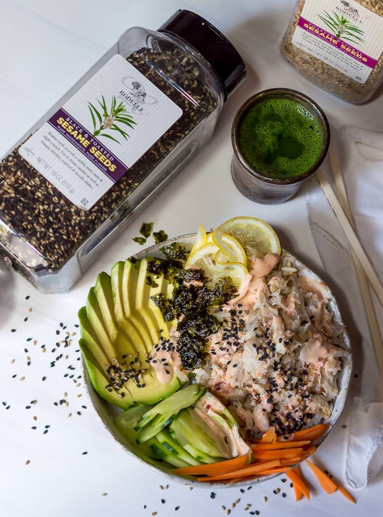 spicy crab sushi bowl next to bottle of black sesame seeds and a cup of green tea