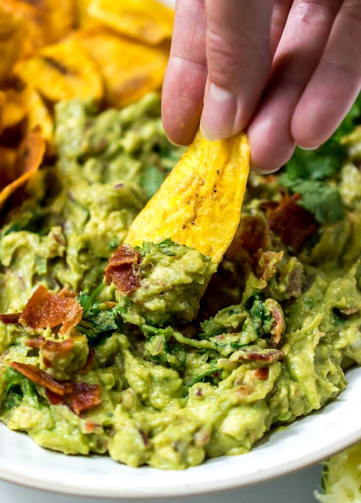 close up photo of plantain chip dipping into bacon guac recipe