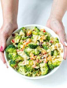 two hands holding white bowl filled with broccoli pasta salad