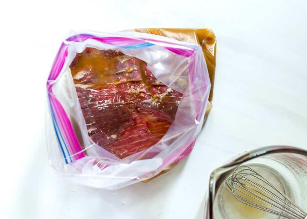 flank steak marinating in plastic ziploc bag