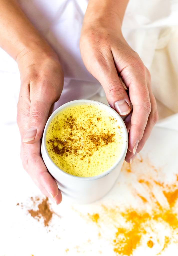 two hands holding a white mug filled with golden milk and cinnamon