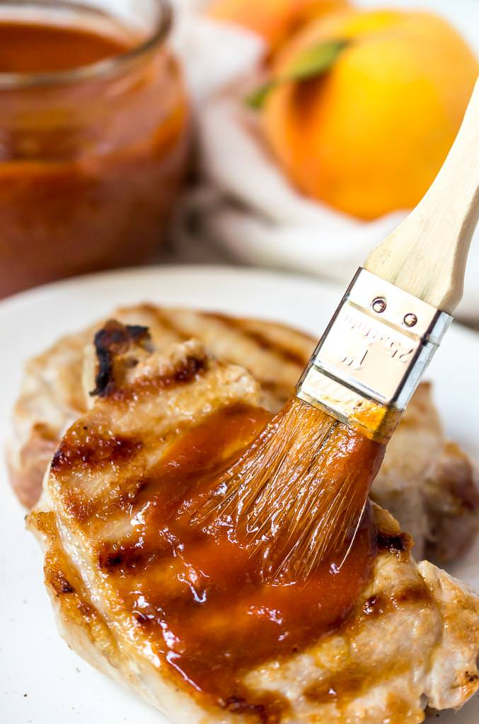 bbq brush slathering peach barbecue sauce onto a grilled pork chop