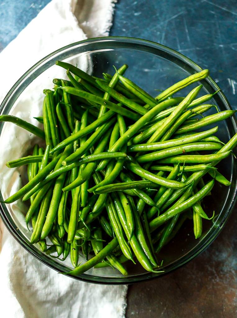 over head photo of fresh green beans in clear glass bowl
