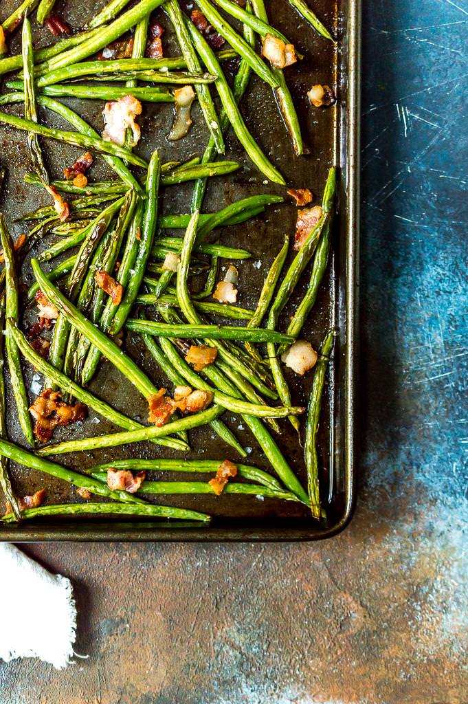 roasted green beans with bacon in a rimmed baking sheet
