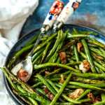 roasted green beans with bacon in blue dish with serving utensils