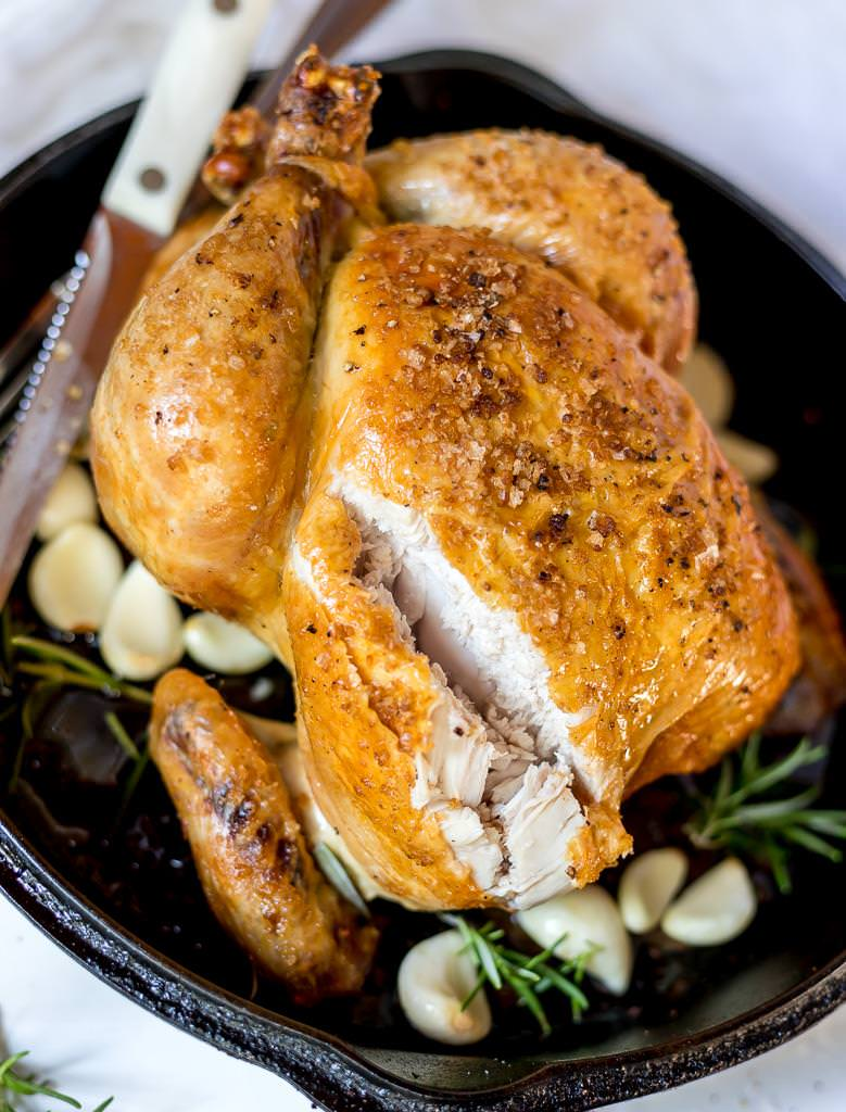 carved whole roast chicken with knife in the background