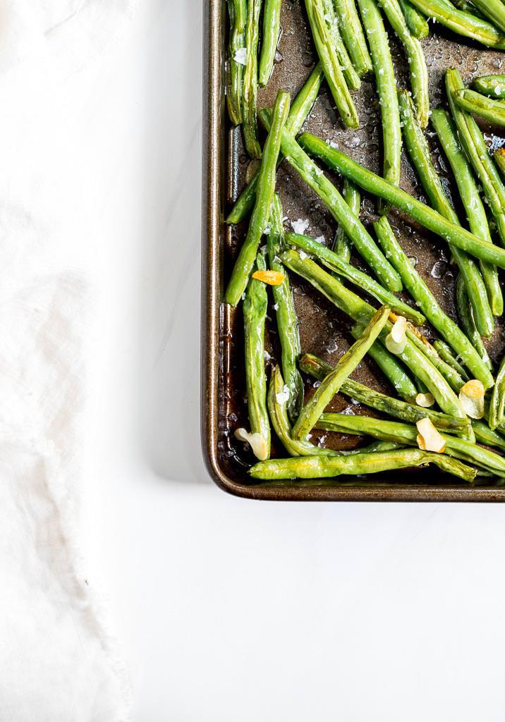 roasted fresh green beans on rimmed baking sheet