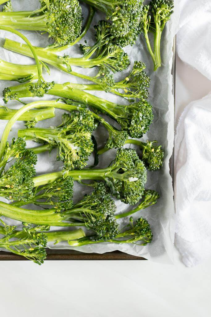 fresh raw broccolini on parchment paper for roasted broccolini recipe