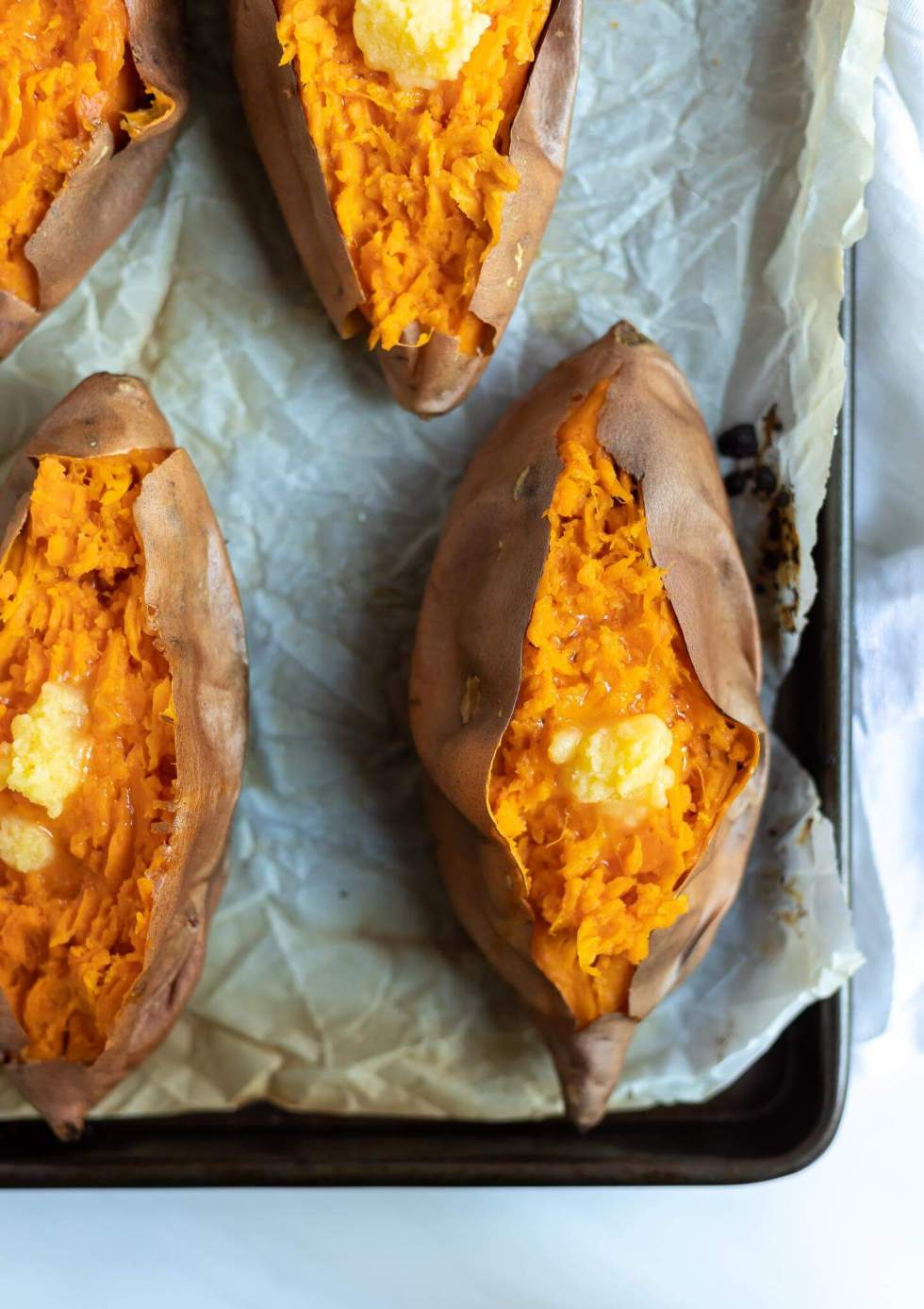 roasted sweet potatoes topped with ghee on parchment paper