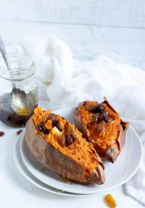 two sweet potatoes topped with honey and raisins on white plate