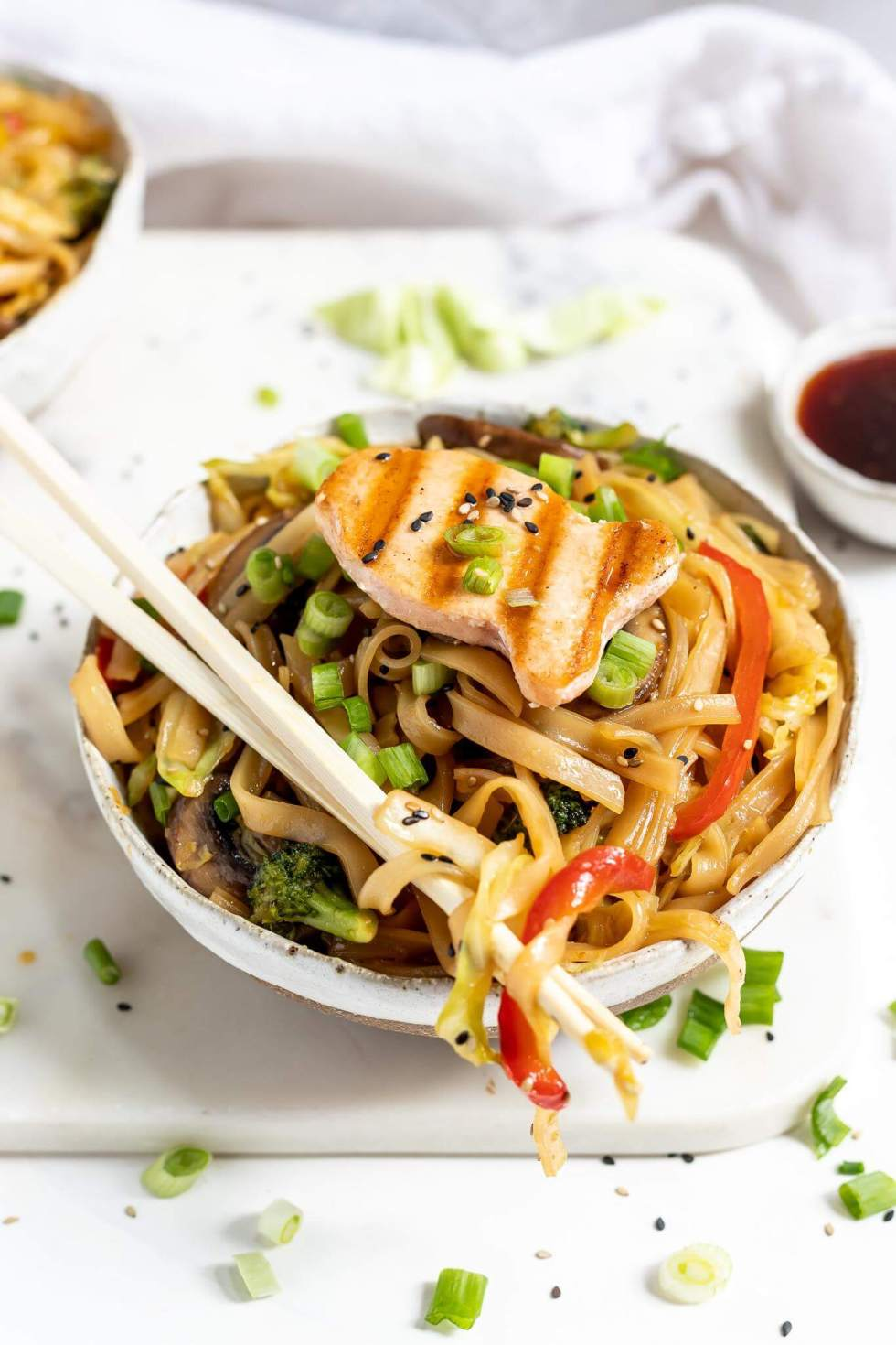 bowl of chinese noodles with chopsticks on top