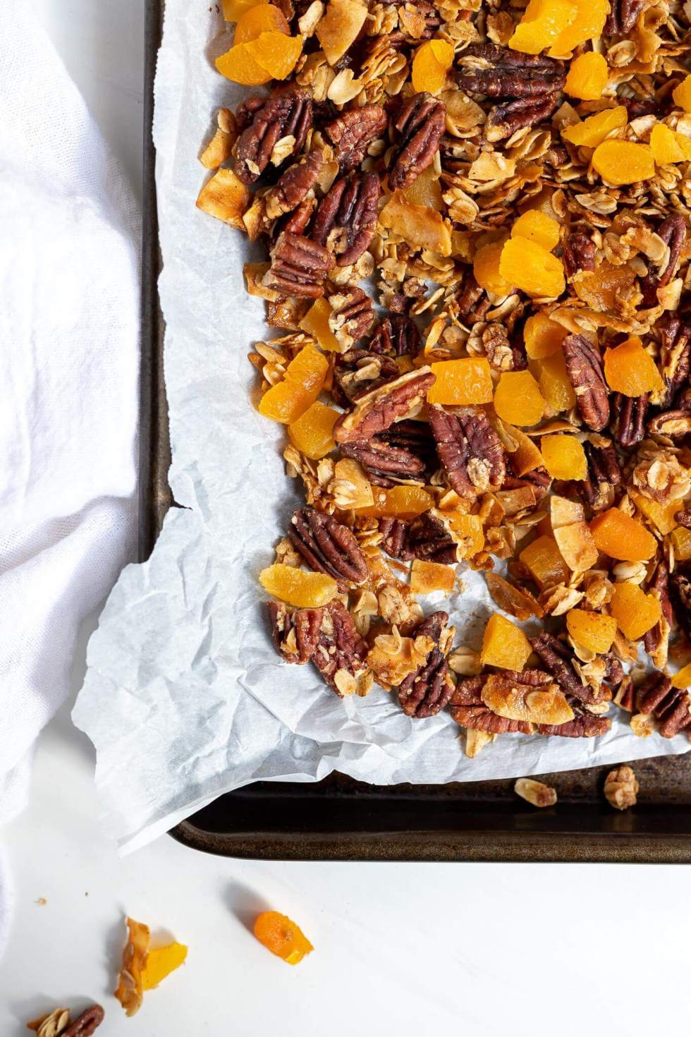 homemade granola with pecans and apricots on baking sheet