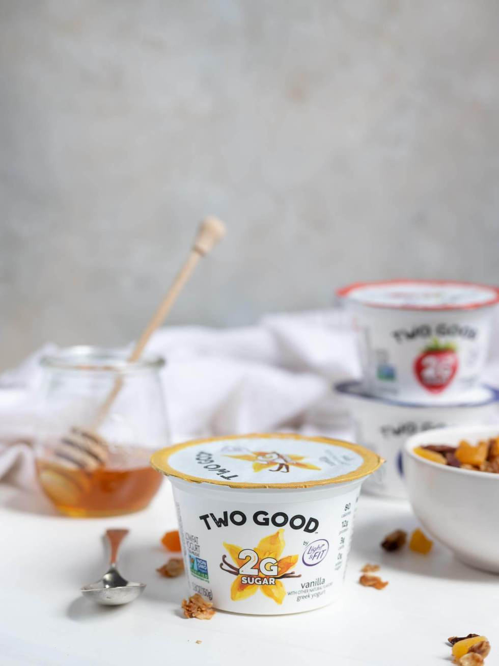 two good yogurt container with honey and homemade granola on the side