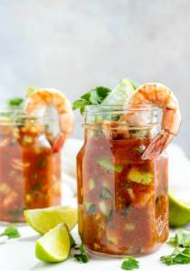 mexican shrimp cocktail served in glass jars, limes on the side