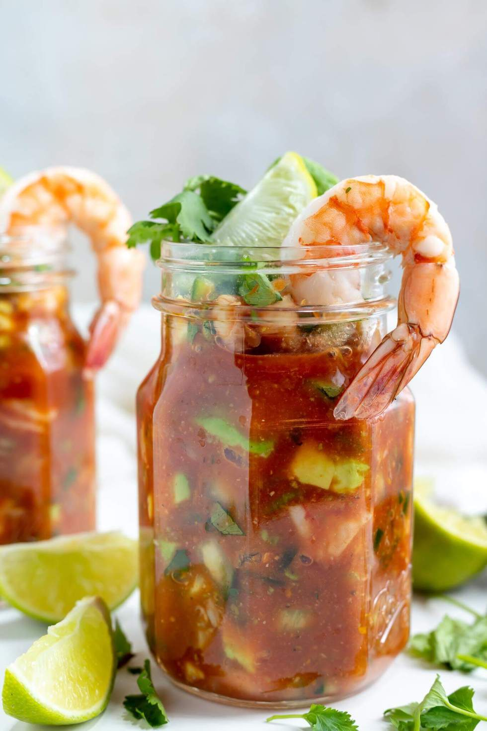 mexican shrimp cocktail in a glass jar topped with a shrimp, lime and cilantro