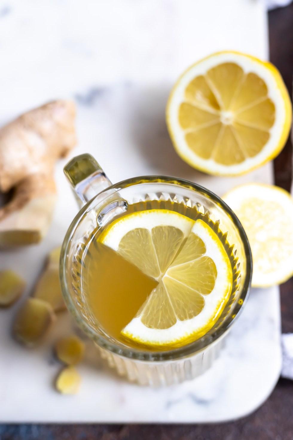 overhead photo of glass mug filled with ginger tea and lemon slices