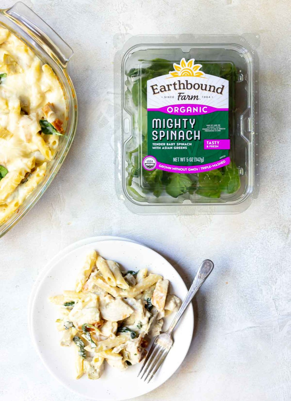 chicken alfredo baked ziti next to container of fresh spinach