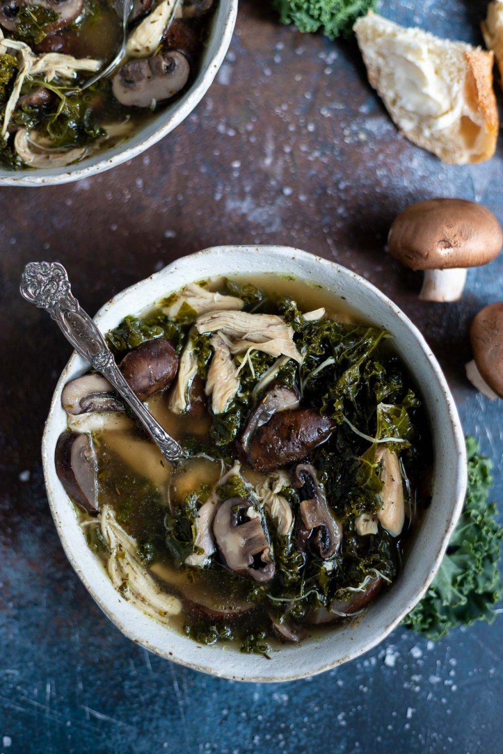 bowl of instant pot chicken soup with mushroom, kale and a golden broth