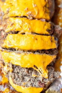 bacon cheeseburger meatloaf topped with orange cheddar cheese and cut into slices to serve