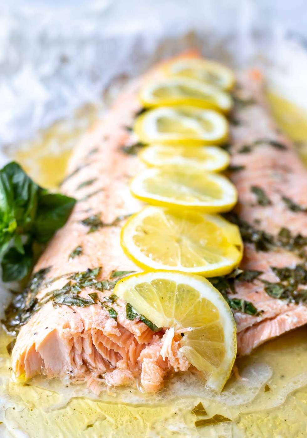 baked salmon topped with fresh chopped basil and sliced lemons