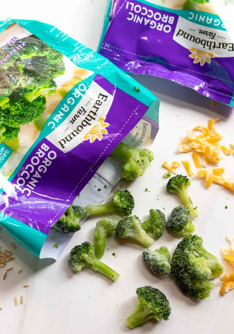 package of frozen broccoli with shredded colby jack cheese on the side