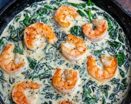 cast iron pan filled with creamed spinach and shrimp