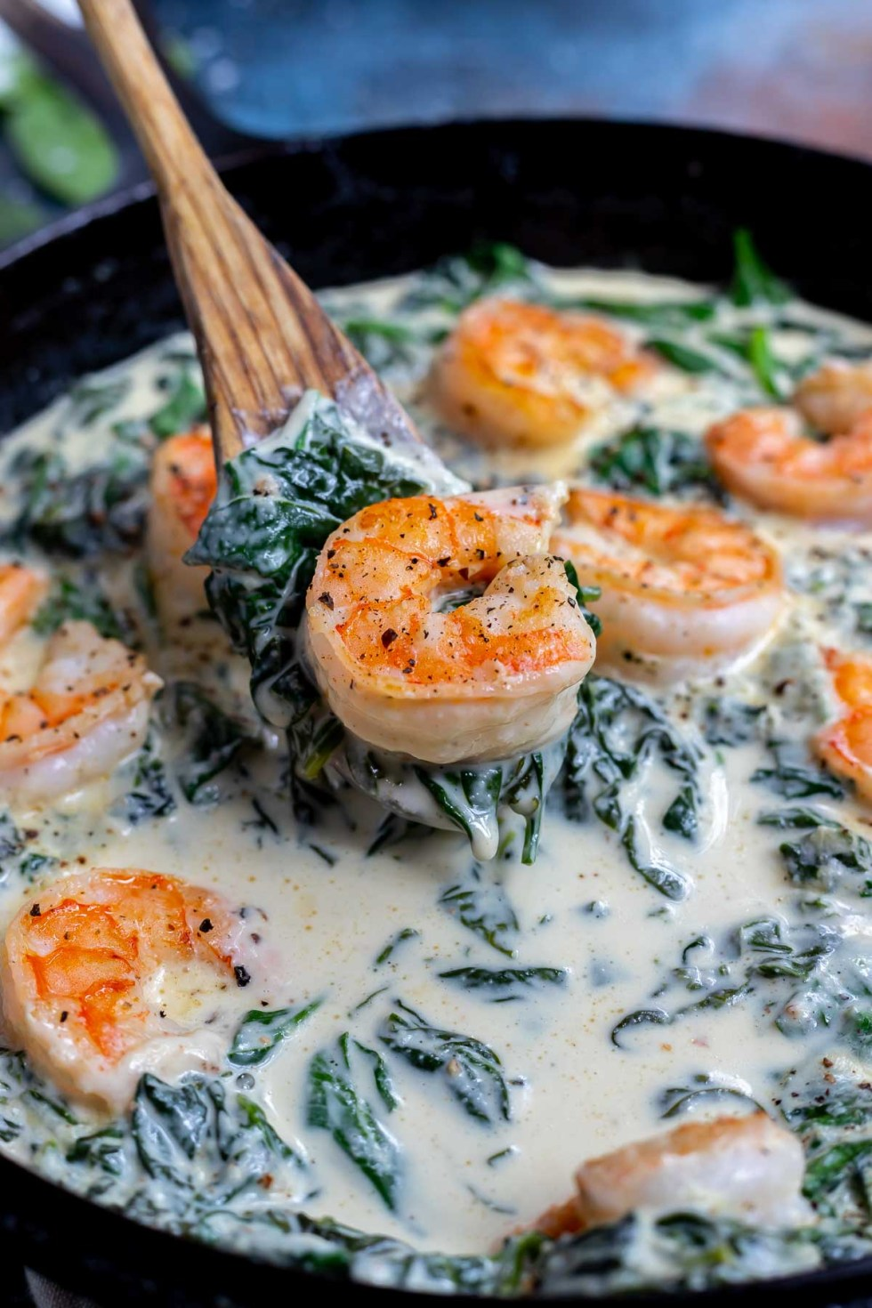 shrimp and spinach in creamy sauce being served with a wooden spoon