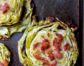 roasted cabbage steak topped with bacon on a dark baking sheet