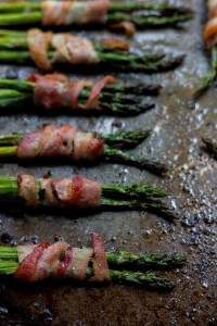 asparagus wrapped in bacon on rimmed baking sheet