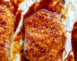 baked pork chop slathered with bbq sauce on parchment paper