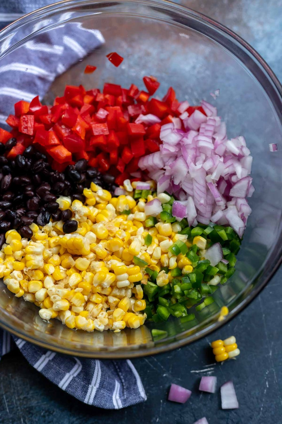 corn, black beans, onions and peppers in clear glass bowl