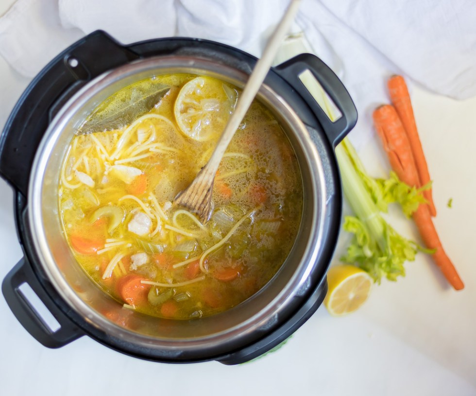 chicken soup in pressure cooker with wooden spoon