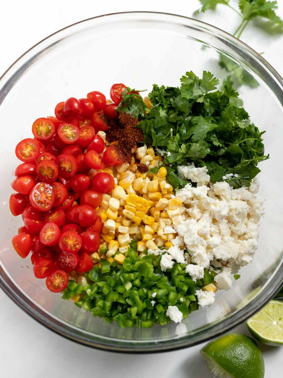 street corn salad ingredients in clear glass bowl