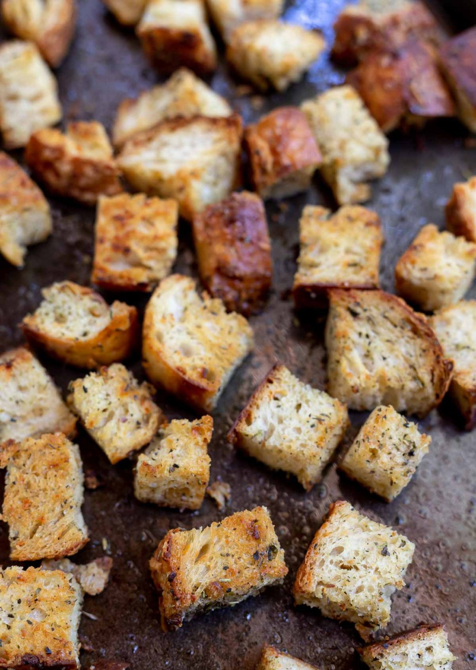baked croutons on dark rimmed baking sheet