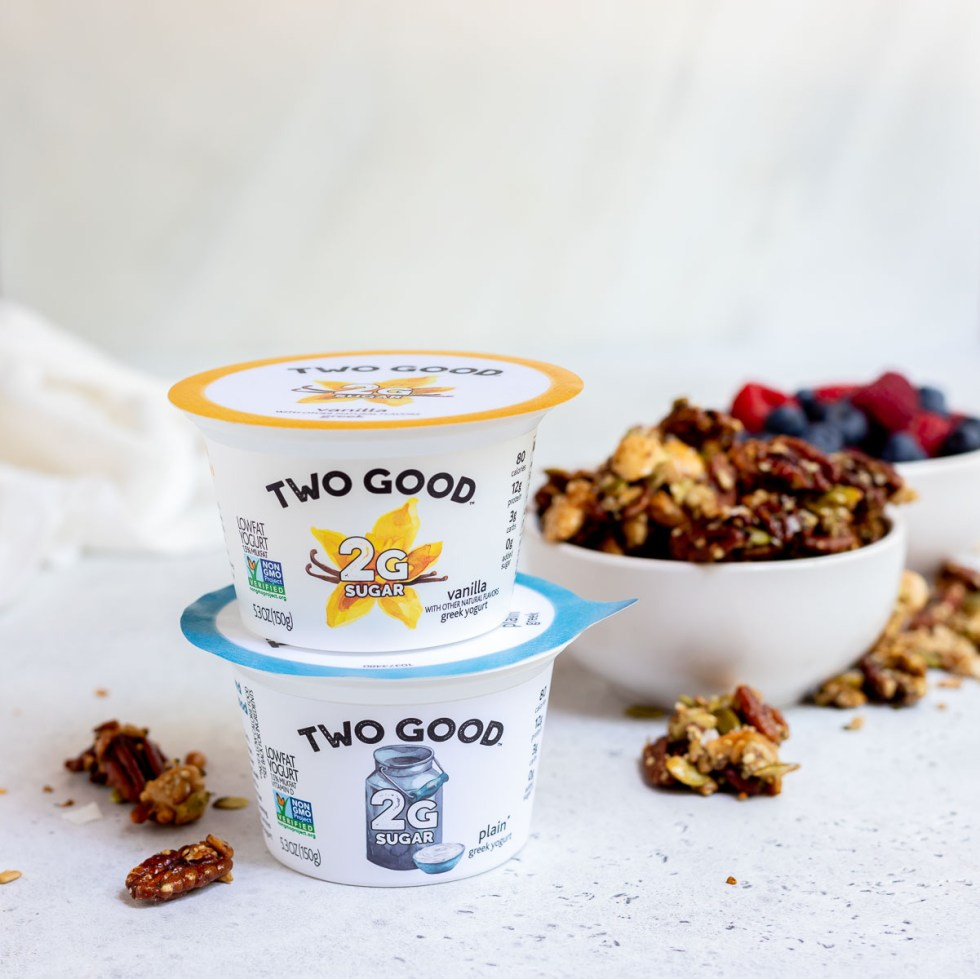 yogurt cups next to granola and berries