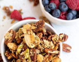 keto granola and fresh berries in white bowls