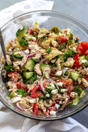 tuna salad ingredients mixed together in clear glass bowl