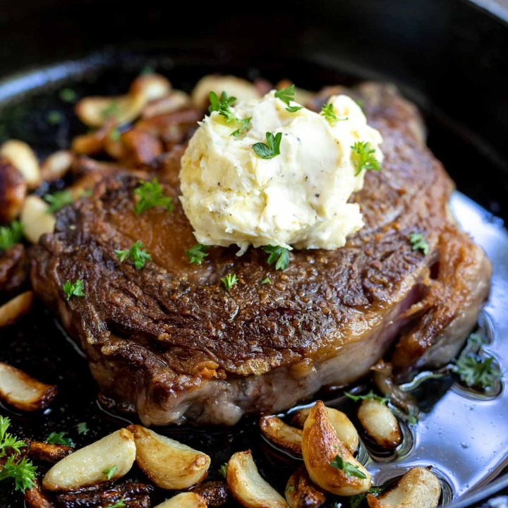 seared ribeye steak in cast iron pan with garlic cloves