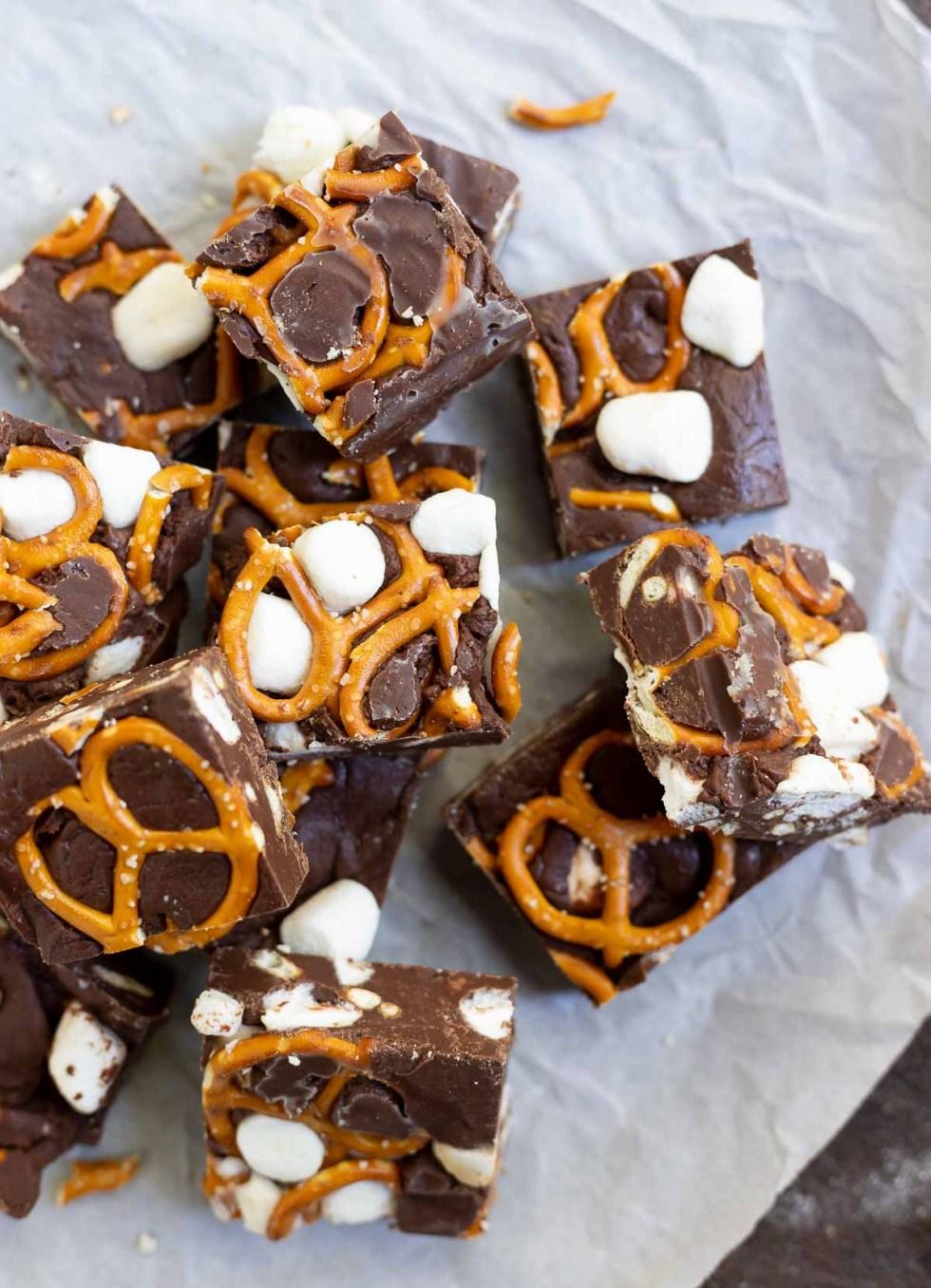 cut chocolate pretzel fudge squares on parchment paper