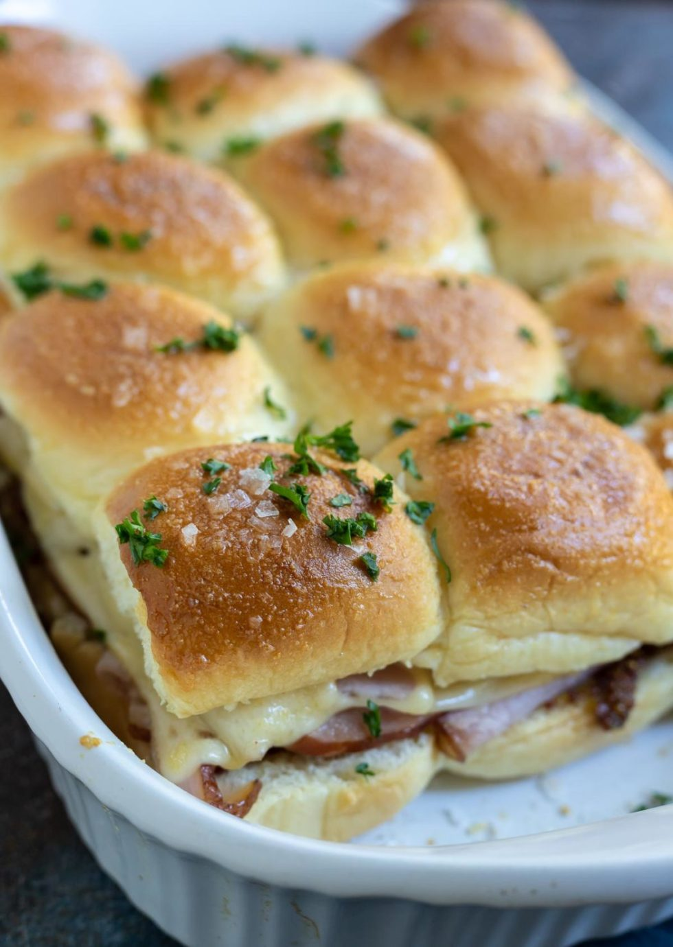 baked ham and cheese sandwiches in white casserole dish