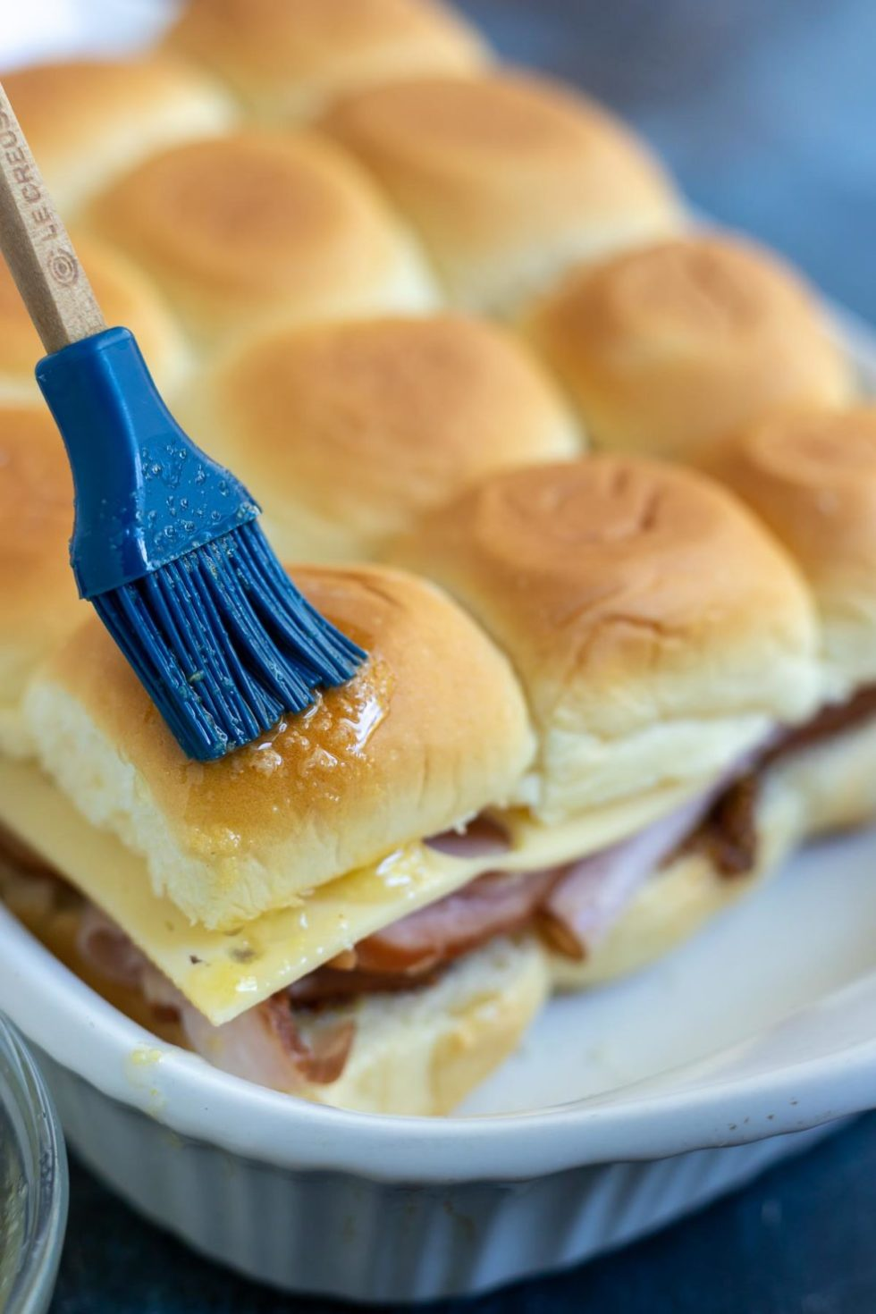 sandwich rolls being brushed with melted butter